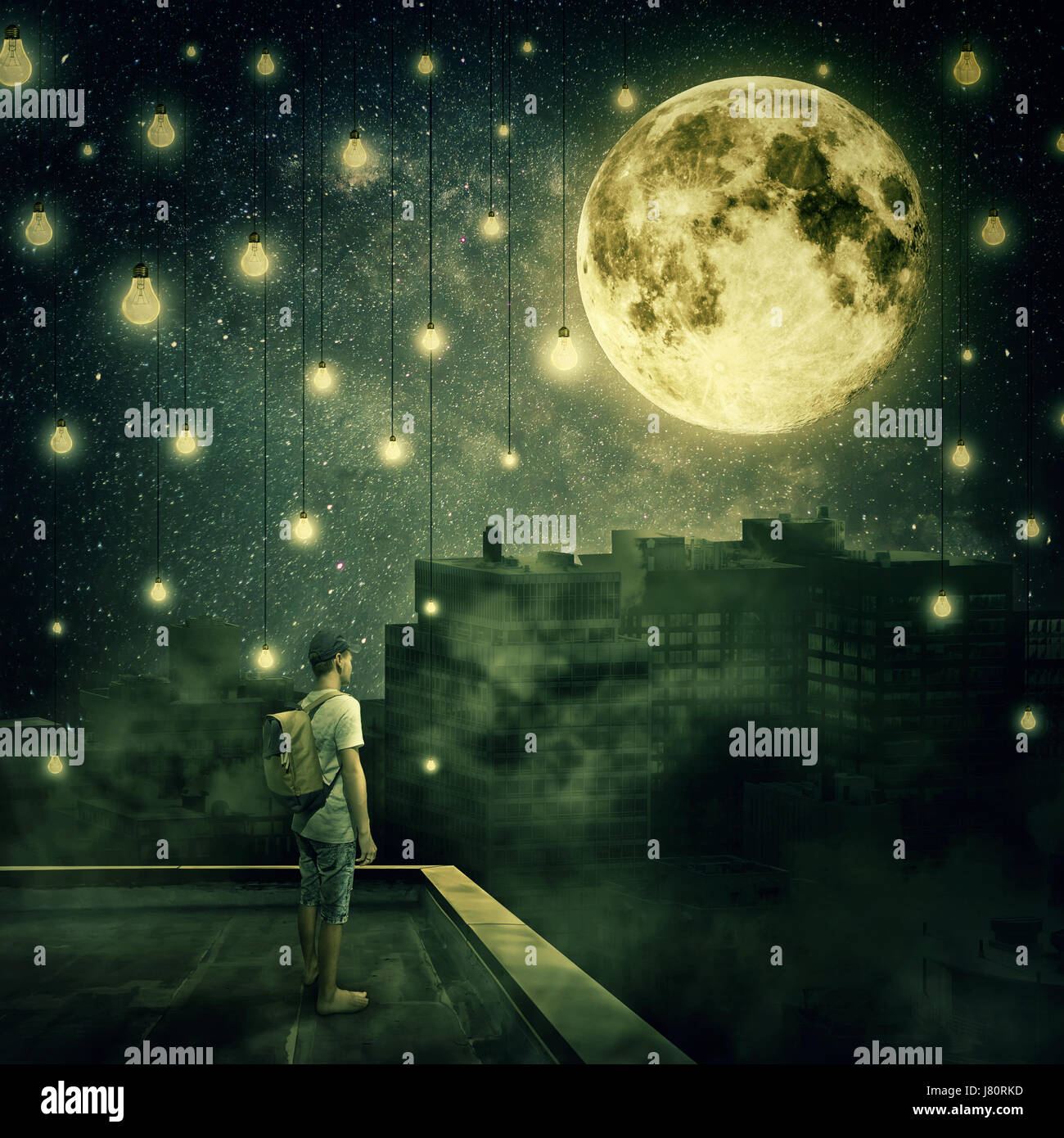 Young boy stay on the rooftop looking at the full moon. Mysterious night with suspended lightbulbs as stars over - Stock Image