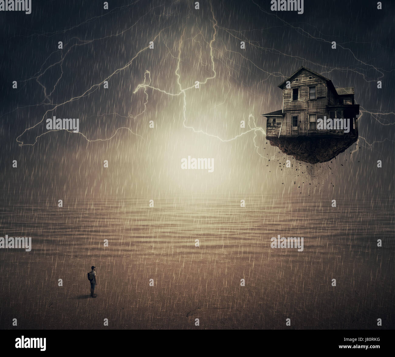 Surreal backround of a man standing in the rain, in front of a flying house ripped from the ground, near the ocean. - Stock Image