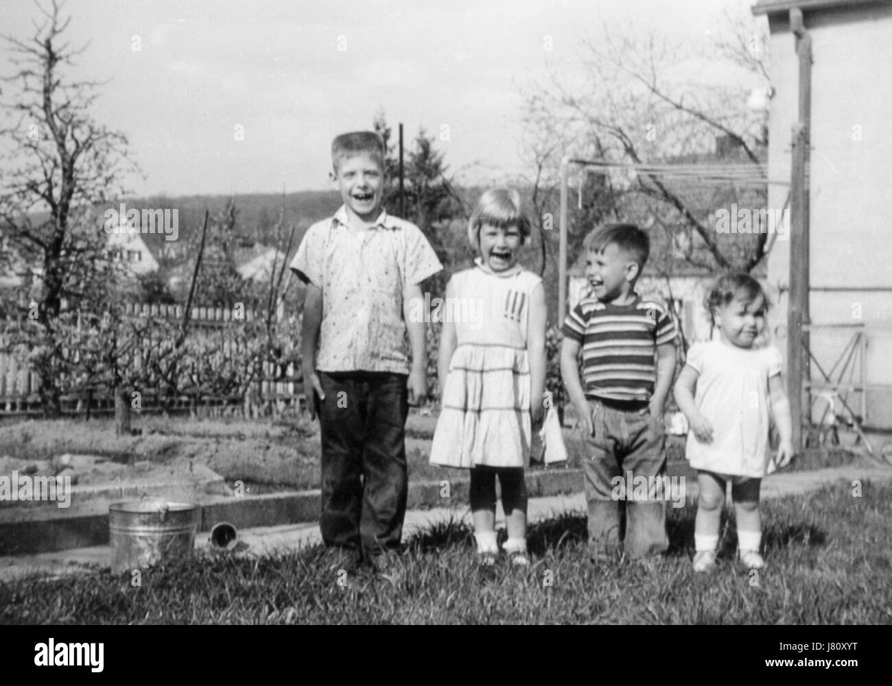1950's Stair-step  Four Children Posing in Backyard, USA - Stock Image