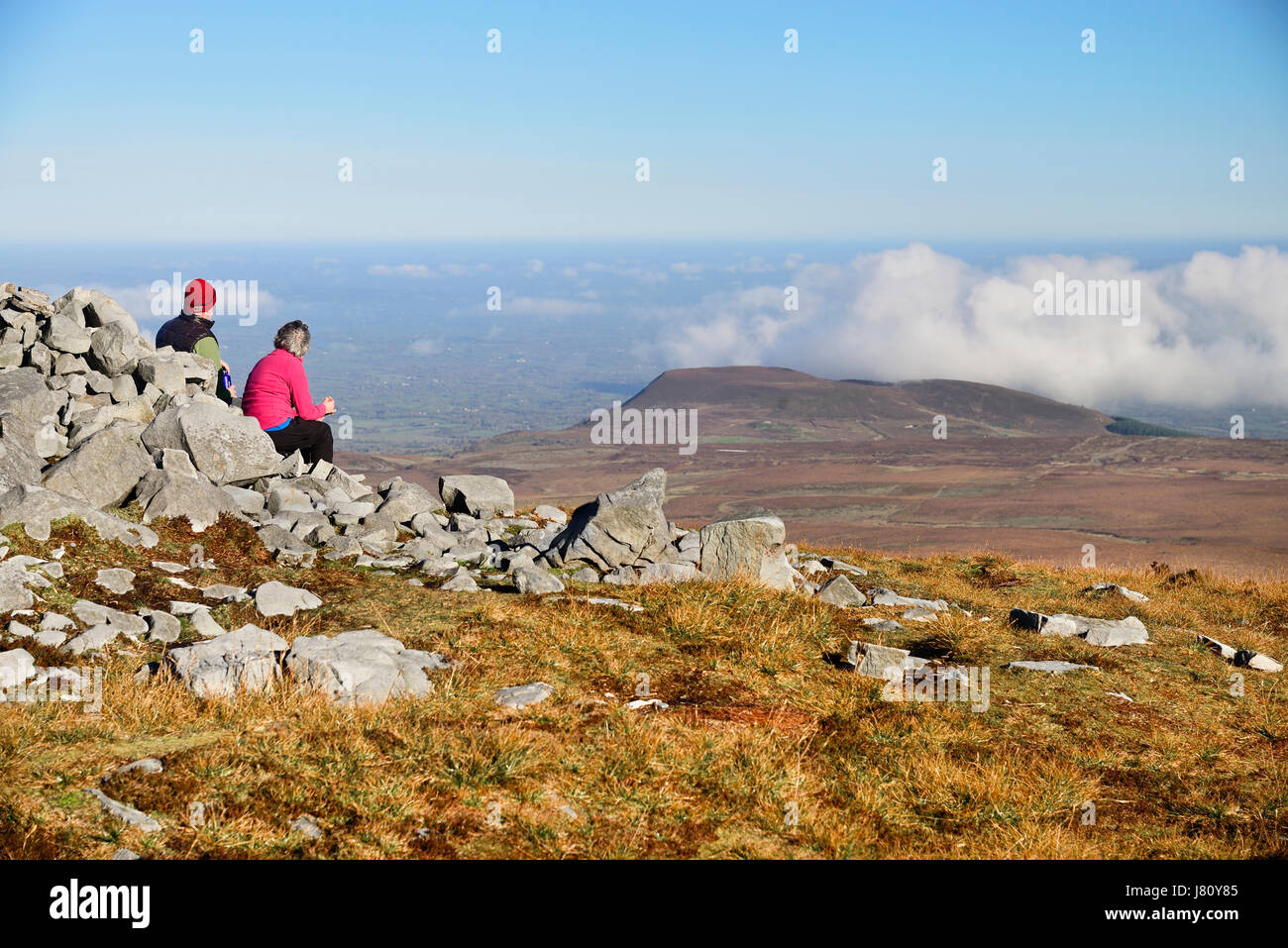Ireland, County Fermanagh, Cuilcagh Mountain Park, Hikers sitting at the edge of a prehistoric cairn enjoying the - Stock Image