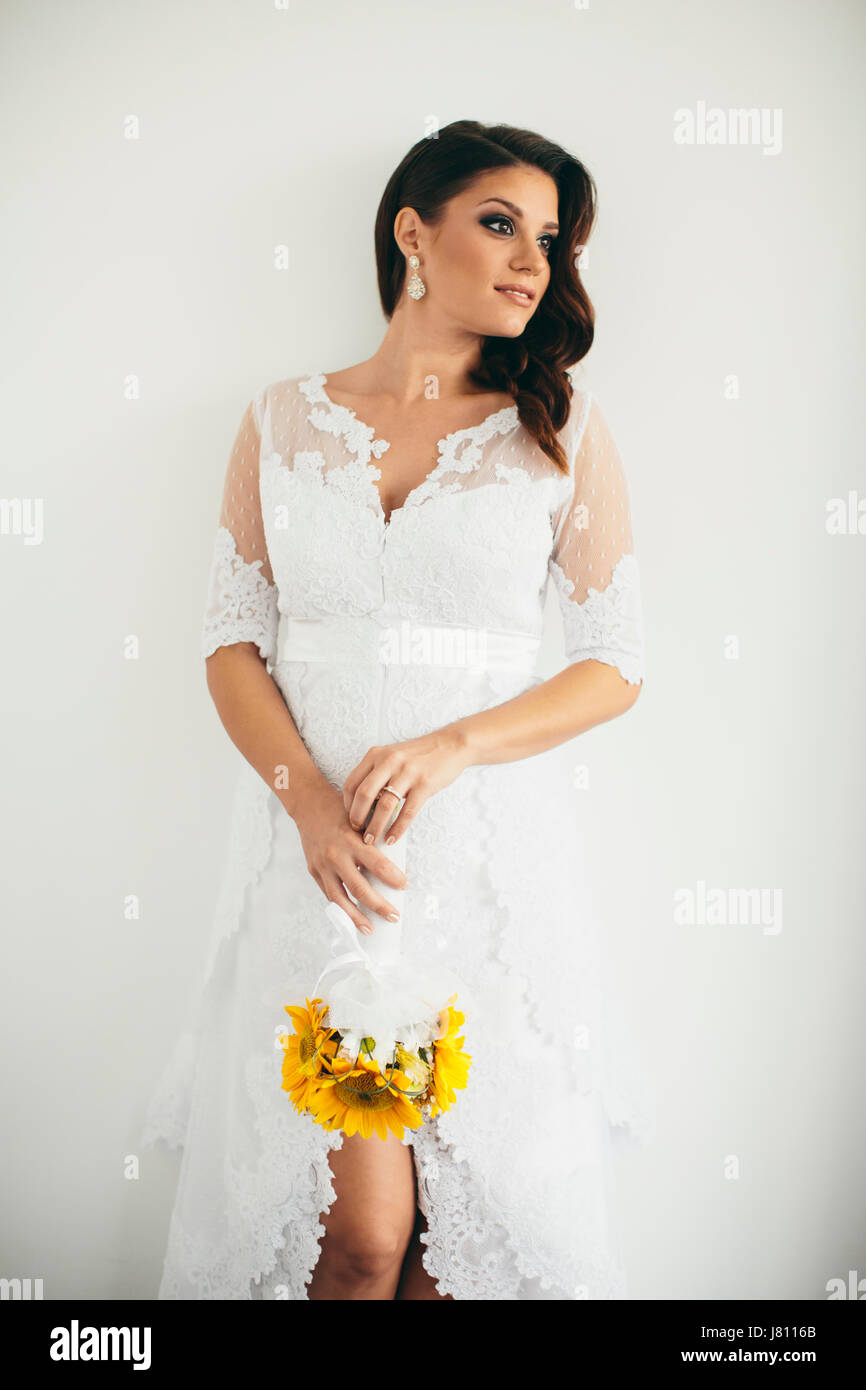 Beautiful Young Bride Posing In A Wedding Dress And Holding A