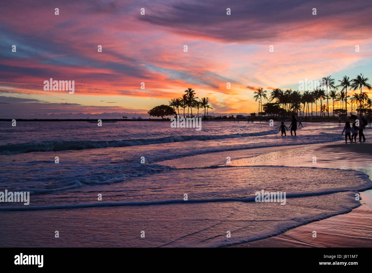 Colorful sunset from the beach in front of the Hilton Hawaiian village on Waikiki Beach in Oahu. - Stock Image