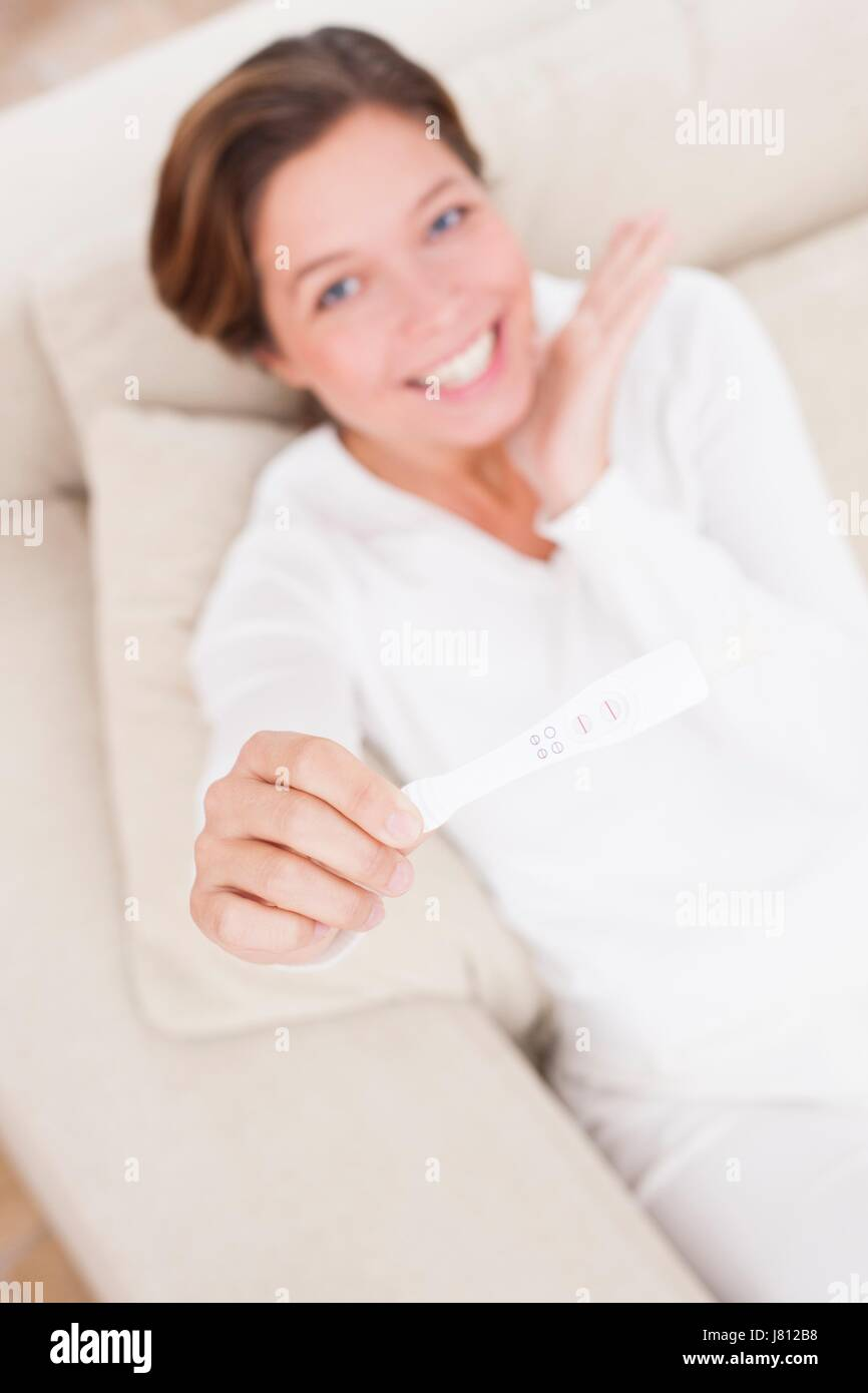Woman holding positive pregnancy test. - Stock Image