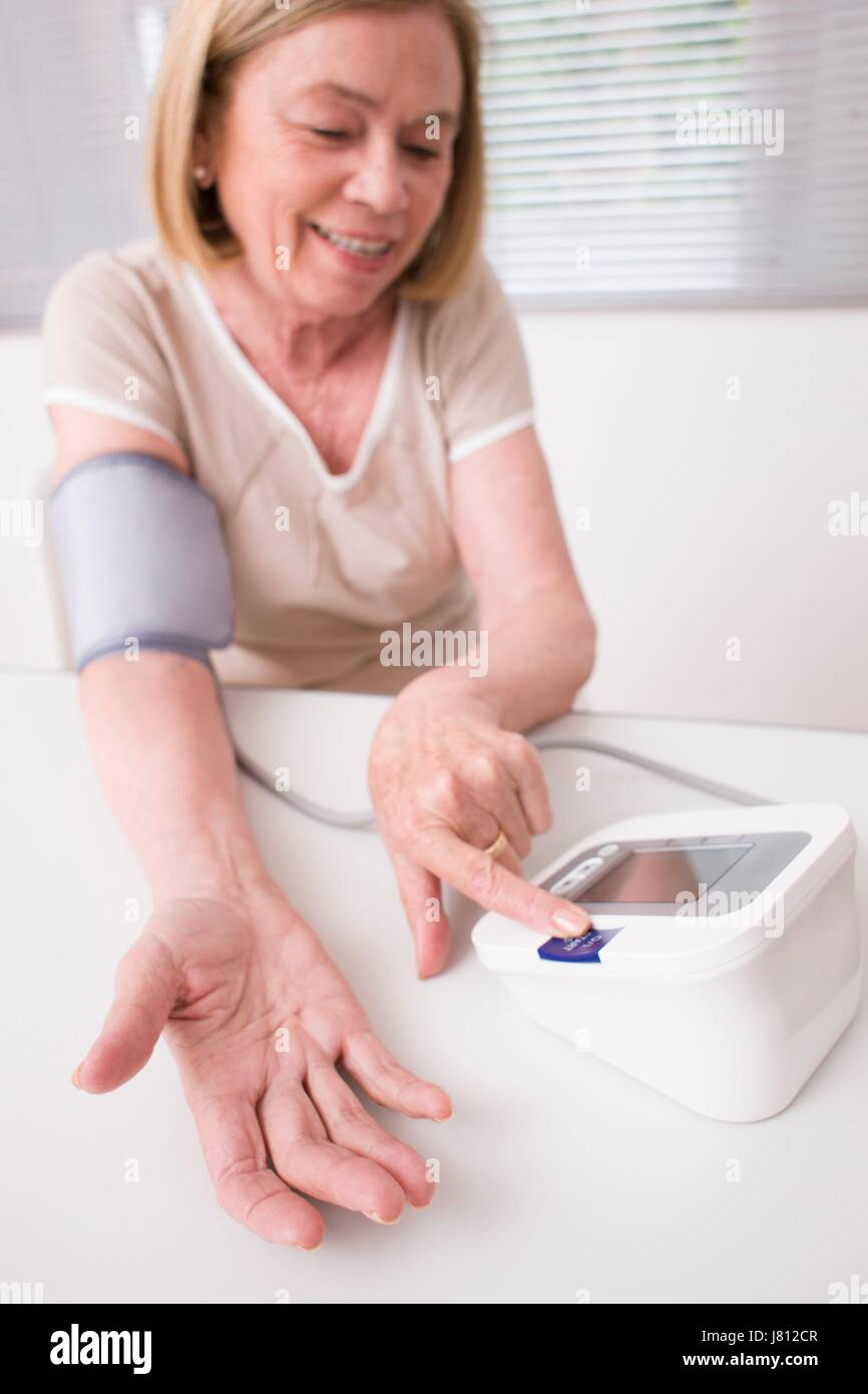 Woman taking her own blood pressure. - Stock Image