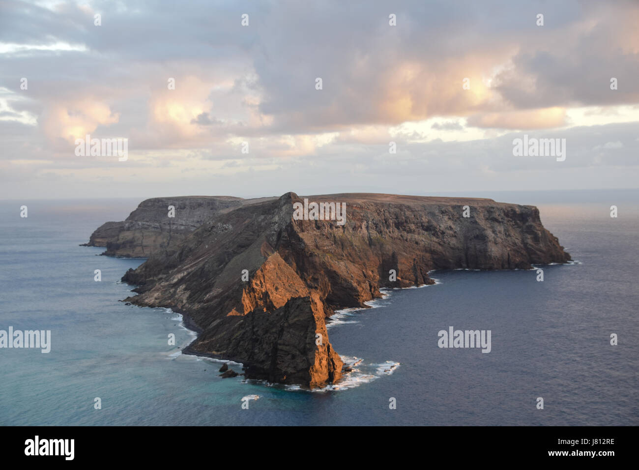 Sunset reflecting on Ilheu da Cal uninhabitated island to the south of Ponta Da Calheta, Porto Santo with Madeira - Stock Image