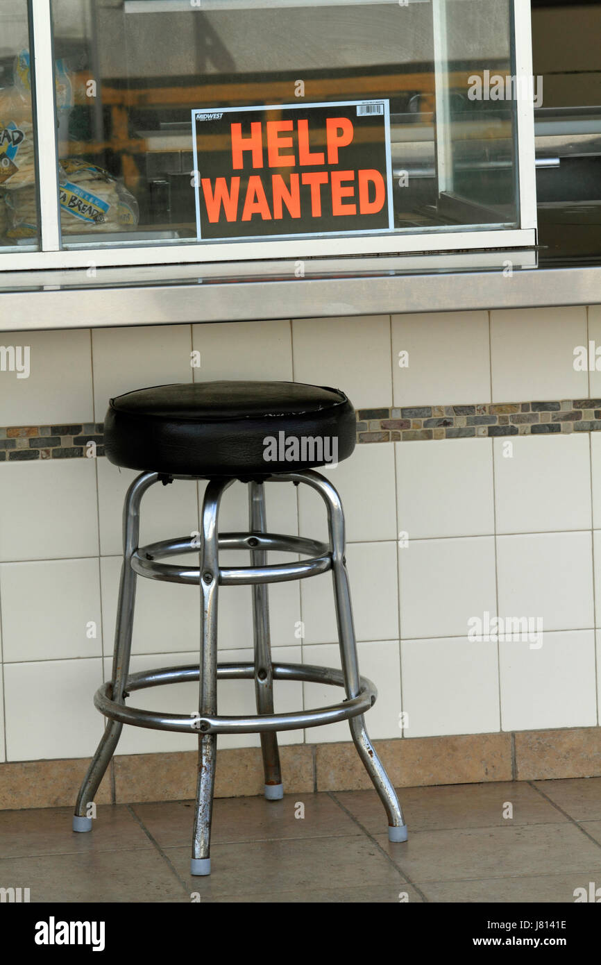 An empty chair at a help wanted sign - Stock Image