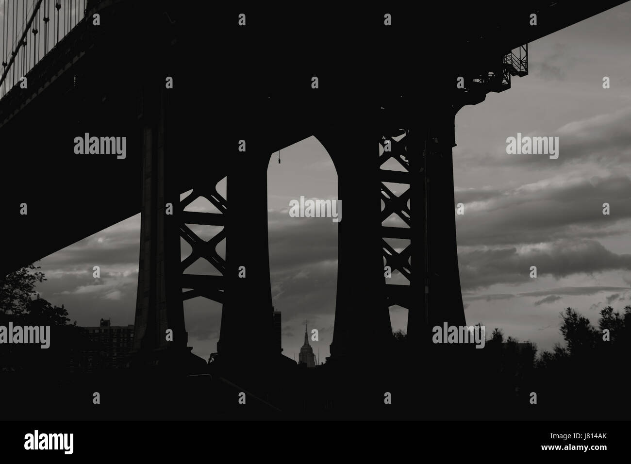 Empire State Building seen through the supporting pier legs of the Manhattan Bridge from DUMBO in Brooklyn, New Stock Photo