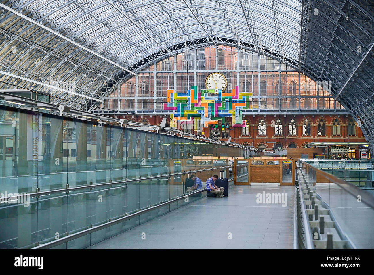 England, London, St Pancras railway station on Euston Road, man with suitcase sits on concourse awaiting his train. Stock Photo