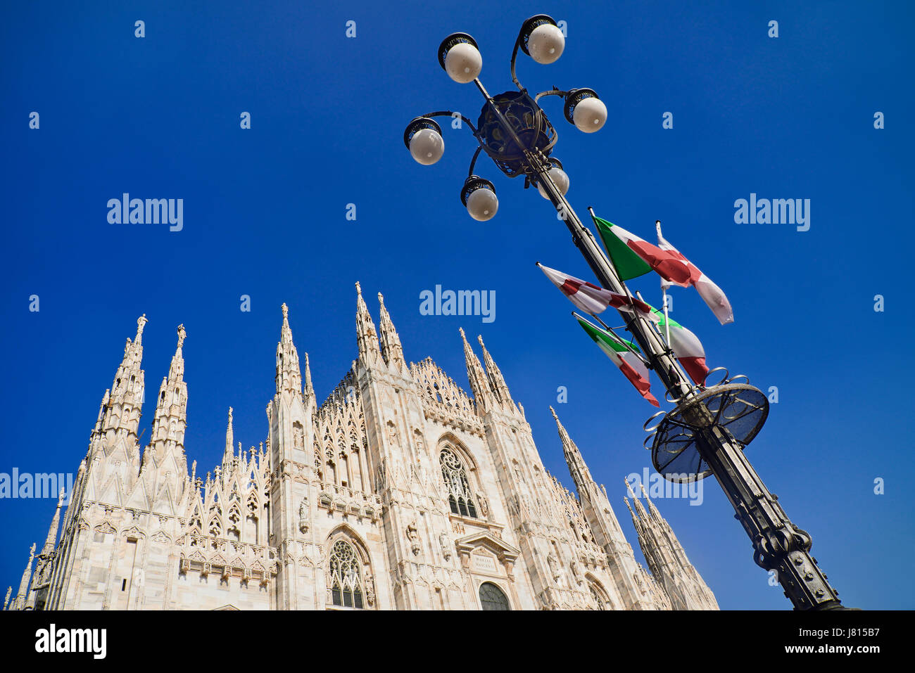 Italy, Lombardy, Milan. Milan Duomo or Cathedral, A section of the facade with a lamp post adorned by Italian flags. - Stock Image