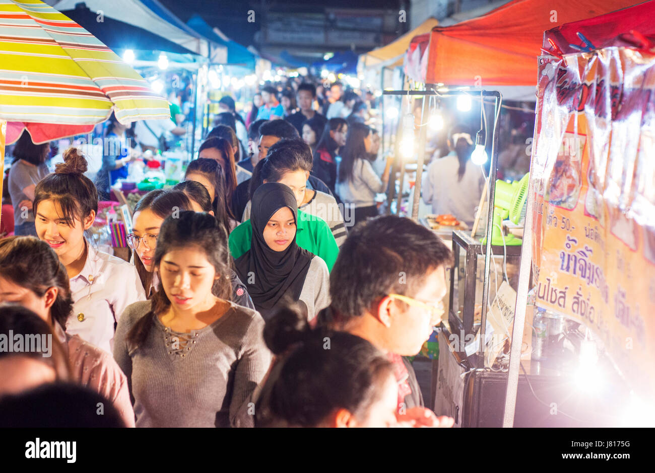 Crowds at a night market near Chiang Rai.  One young Muslim woman among the Buddhist Thais. - Stock Image