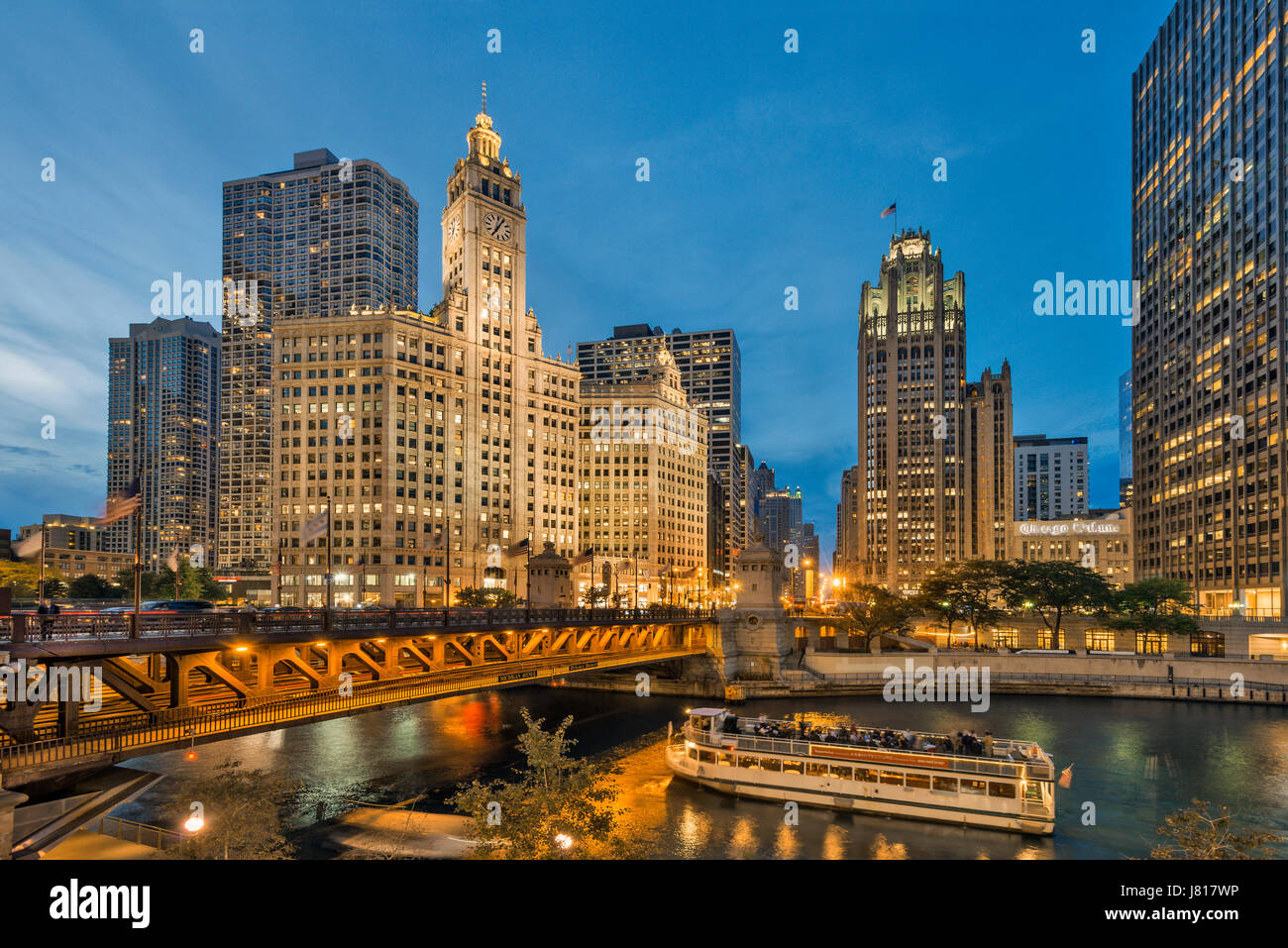 Evening picture of Chicago riverwalk with views of Chicago river, passing boats and already illuminated buildings - Stock Image