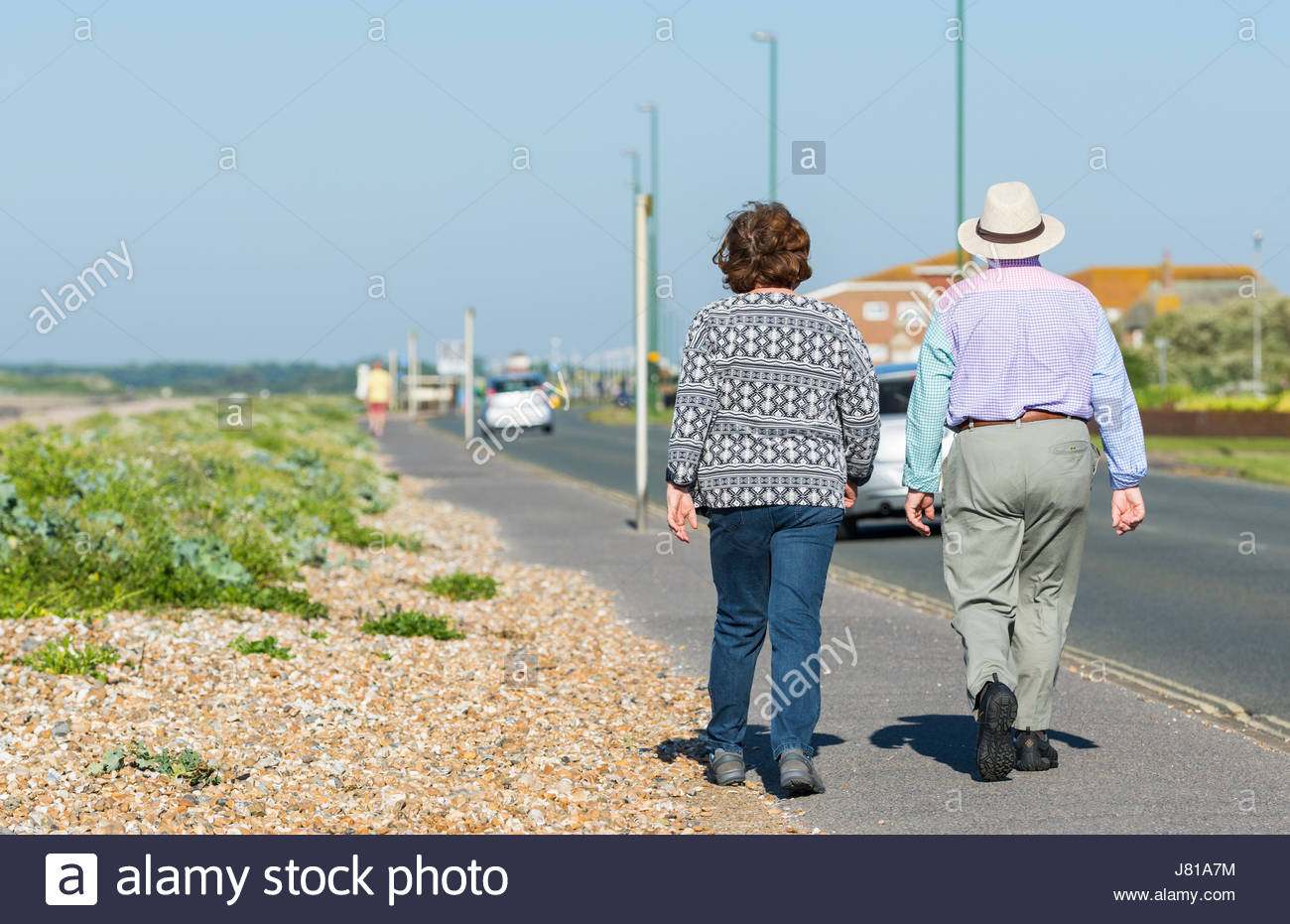 Elderly couple taking a morning stroll along a seafront road in Summer in the UK. - Stock Image