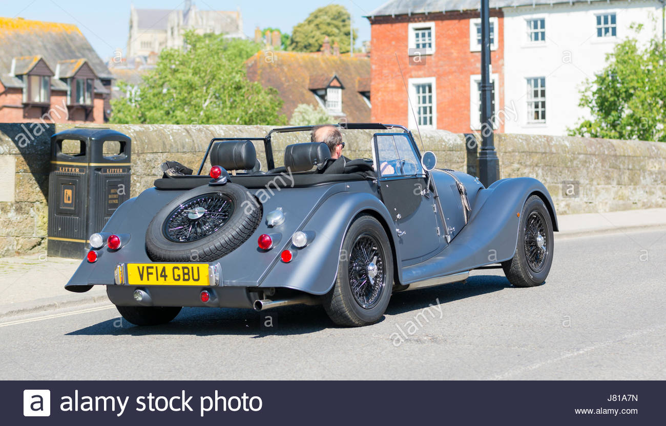 Man driving a convertible sports car with the top down over a bridge on a hot day in the UK. - Stock Image