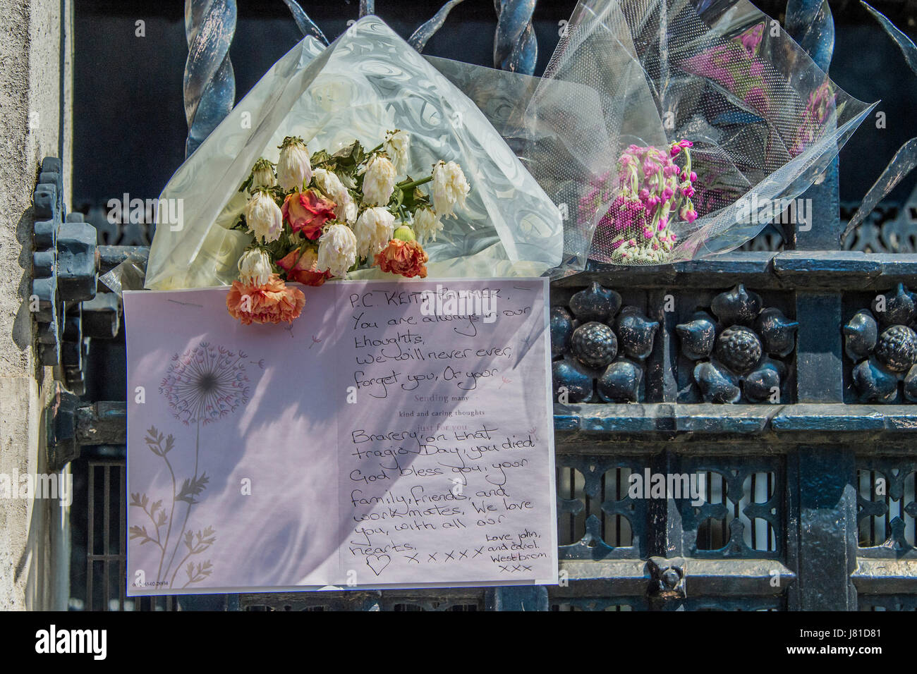 Whitehall, London, UK. 25th May, 2017. A memorial of flowers for PC Keith Palmer remains attatched to the railings - Stock Image
