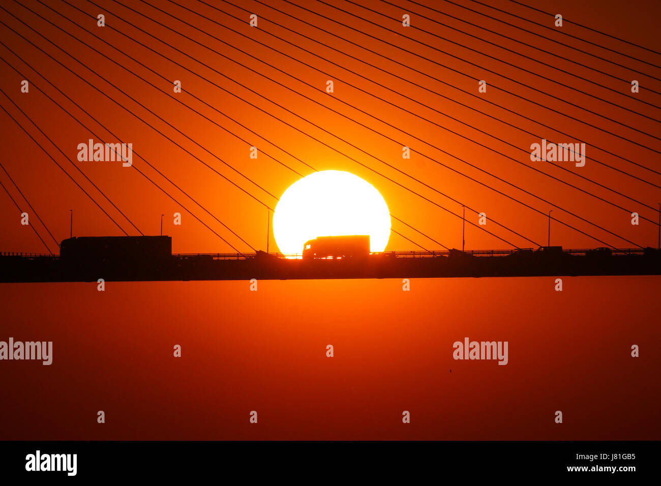 Greenhithe, Kent, United Kingdom. 26th May, 2017. View of the sun setting behind the Queen Elizabeth II Bridge over - Stock Image