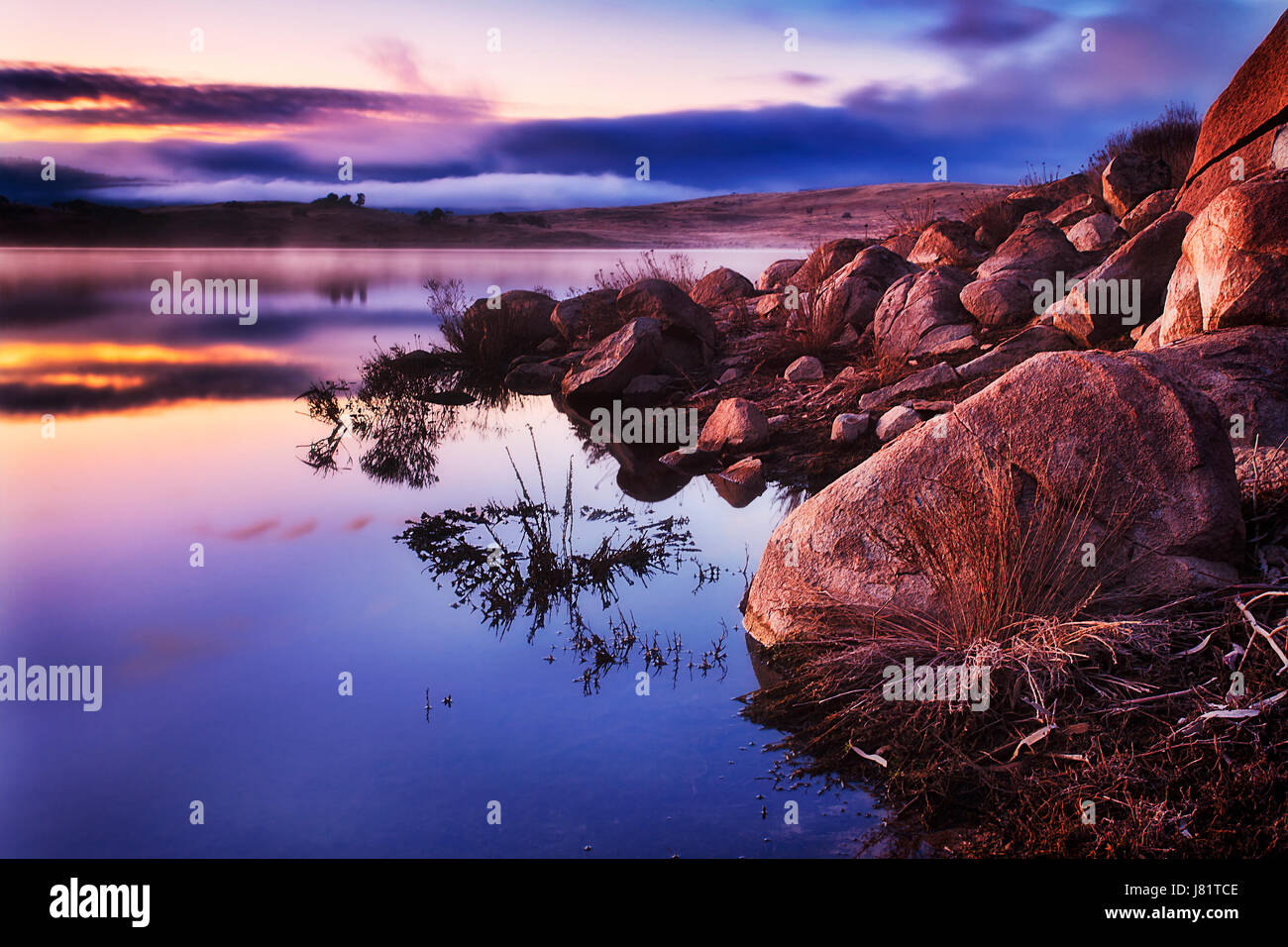 Colourful sunrise on Jindabyne lake in Snowy mountains region of NSW, Australia. Sandstone rocks and boulders on - Stock Image