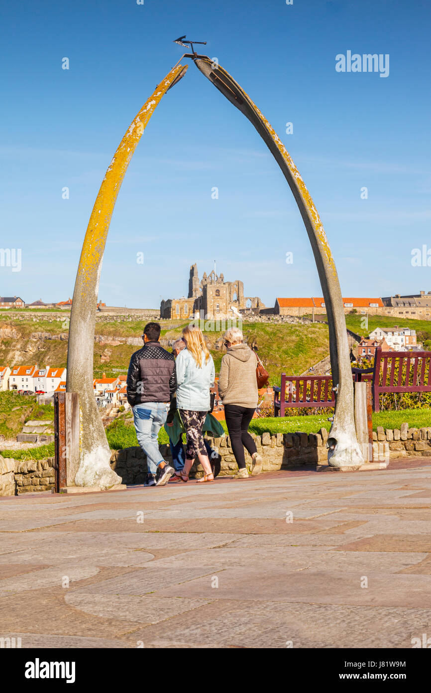 Three people waking through the Whalebone Arch, Whitby, North Yorkshire, England, UK. The bones are from a bowhead - Stock Image