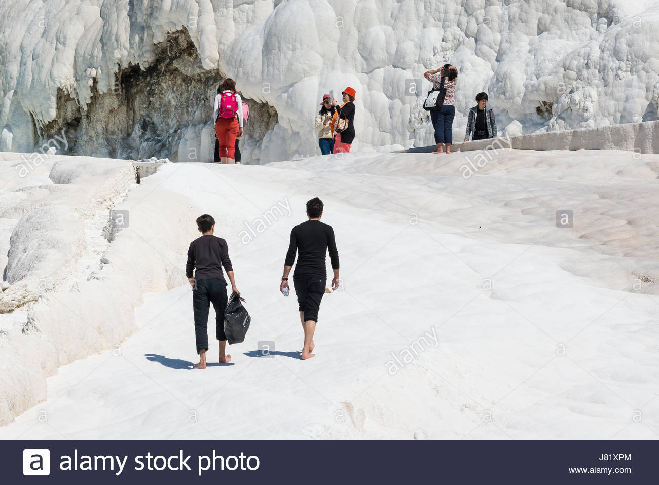 Tourists on Pamukkale travertines in Pamukkale,Turkey. Pamukkale, UNESCO world heritage site, nowadays become one - Stock Image