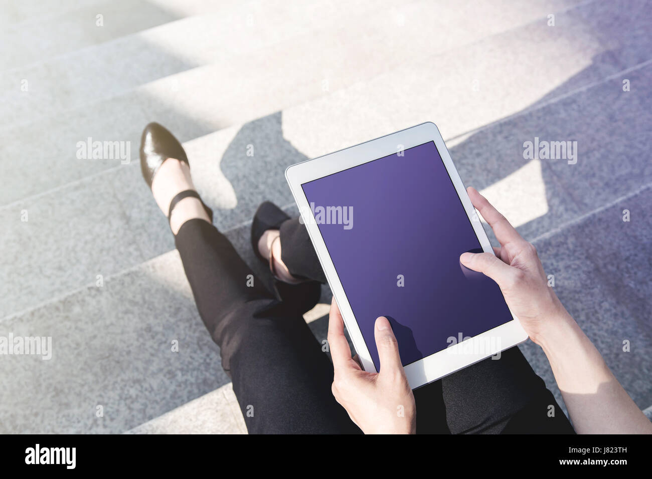 Business working woman sit and using digital tablet mockup at outdoor stair, Top view, Blank screen as clipping - Stock Image