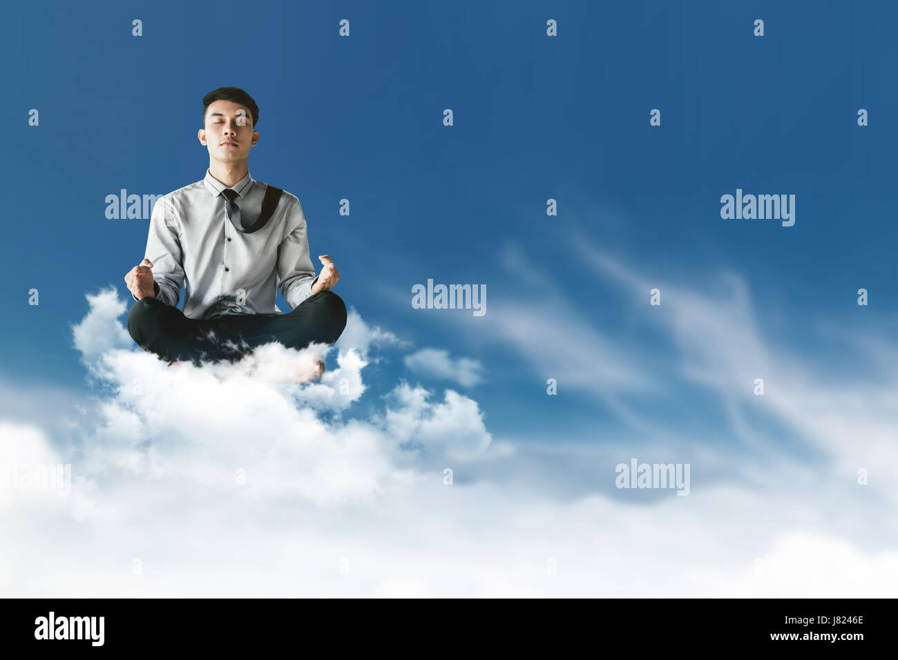 young businessman siting on cloud above the sky with yoga meditation