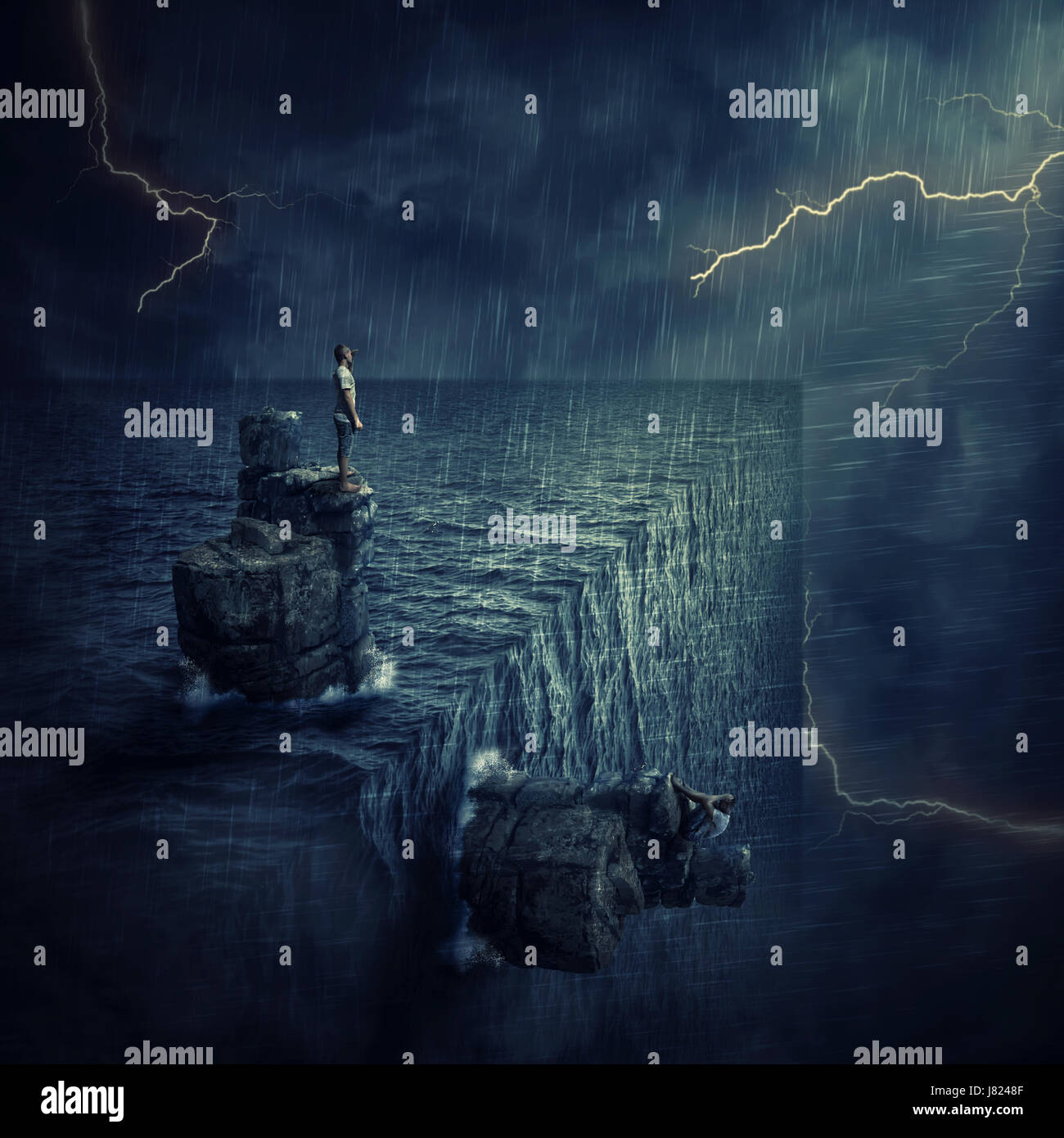 Conceptual image with a lost man sitting on a rock cliff island, in the middle of the ocean, trying to find himself - Stock Image
