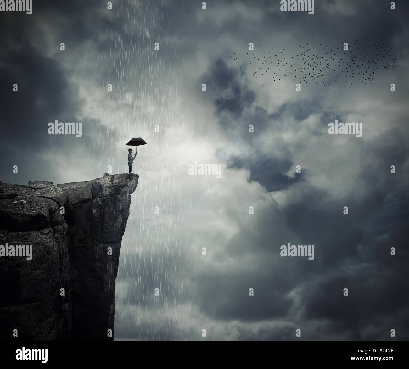 Man with an umbrella stand on the edge of the cliff, calling the rain. Mysterious place above the clouds. - Stock Image