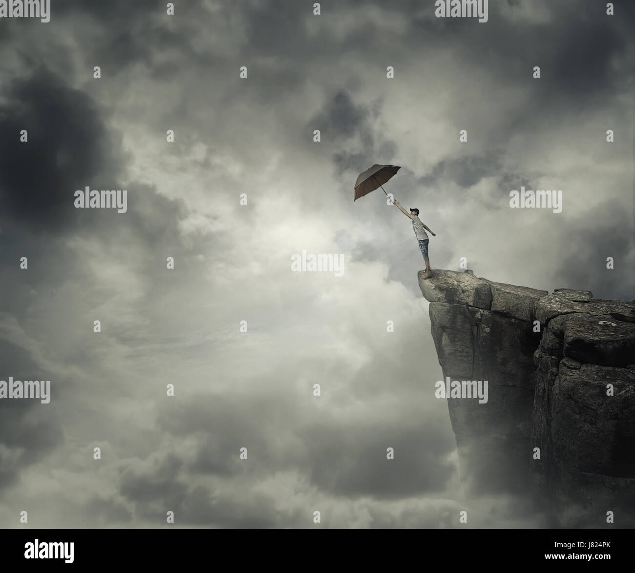 Boy trying to catch his umbrella on the edge of a cliff above the clouds. Escape and fly away. - Stock Image