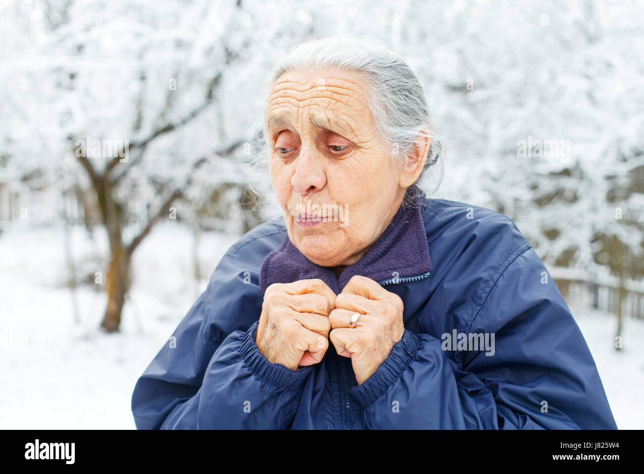 Portrait of a cute old lady feeling cold on wintertime - Stock Image