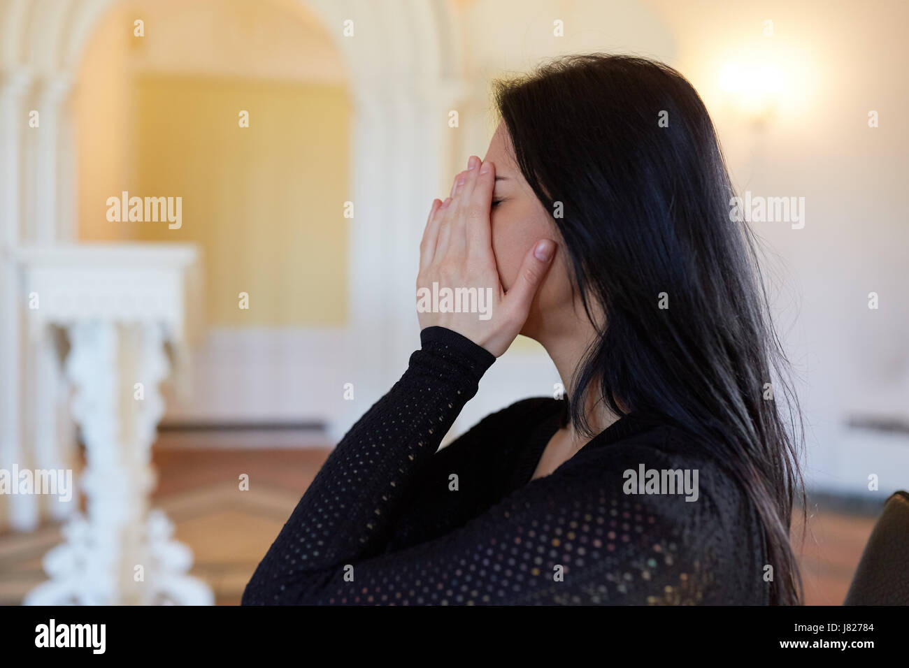 unhappy crying woman at funeral in church - Stock Image