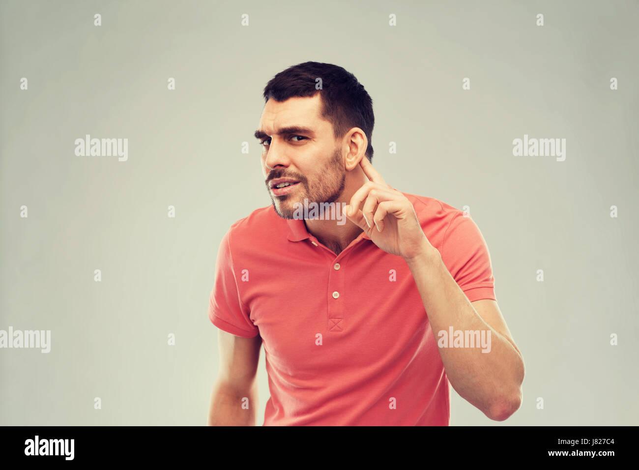 man having hearing problem listening to something - Stock Image