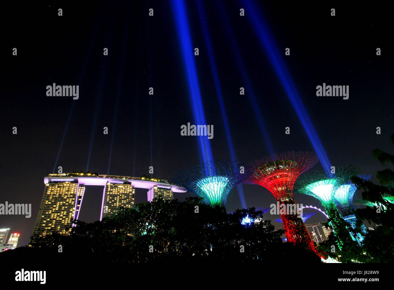 View of Marina Bay Sands and the lighted top of the Supertrees in Gardens by the Bay. - Stock Image