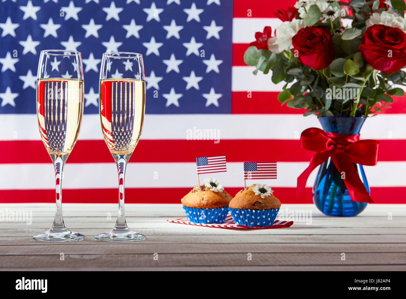 Beautiful bouquet, american flag and two glasses of champagne - Stock Image