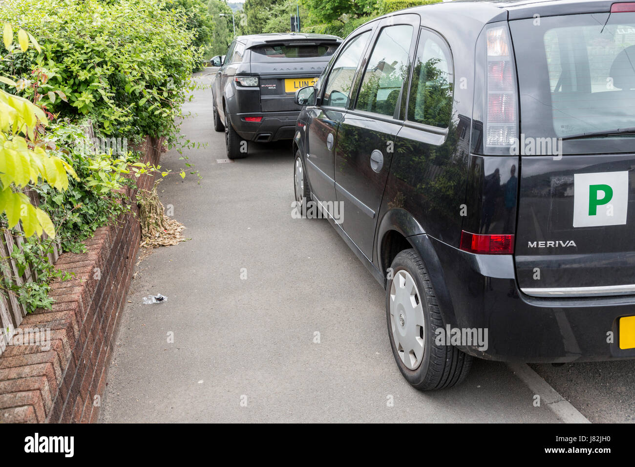 Cars parked on pavement obstructing pedestrian access, Wales, UK - Stock Image