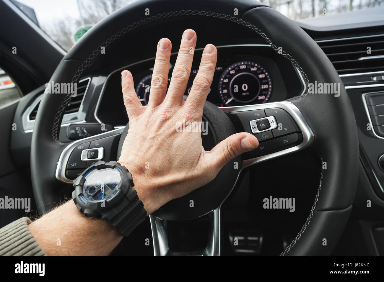 Driver angry pushes a steering wheel klaxon of luxury car. Closeup photo with selective focus - Stock Image