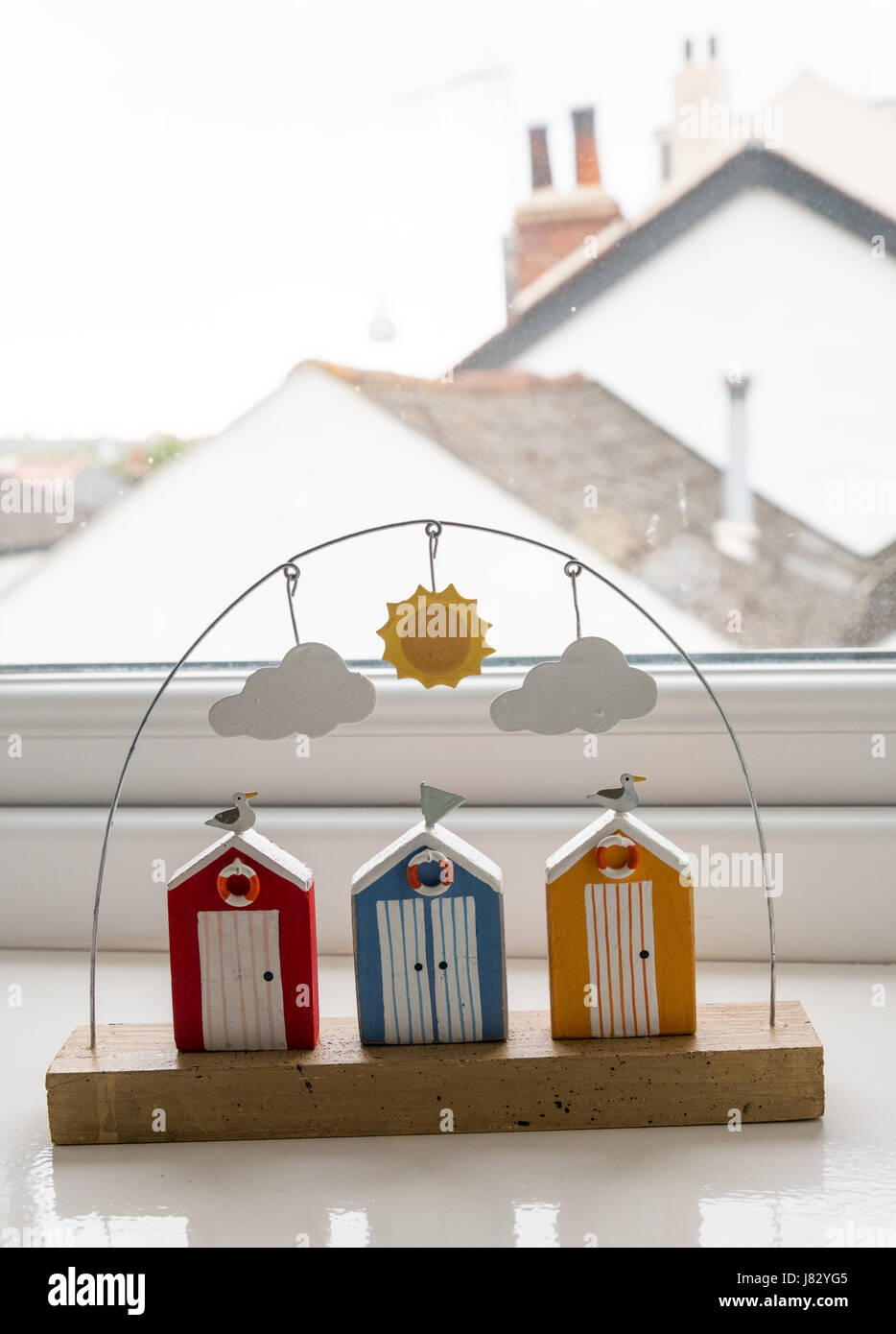 Ornamental row of beach huts with rooftops in the background.  May 2017 - Stock Image