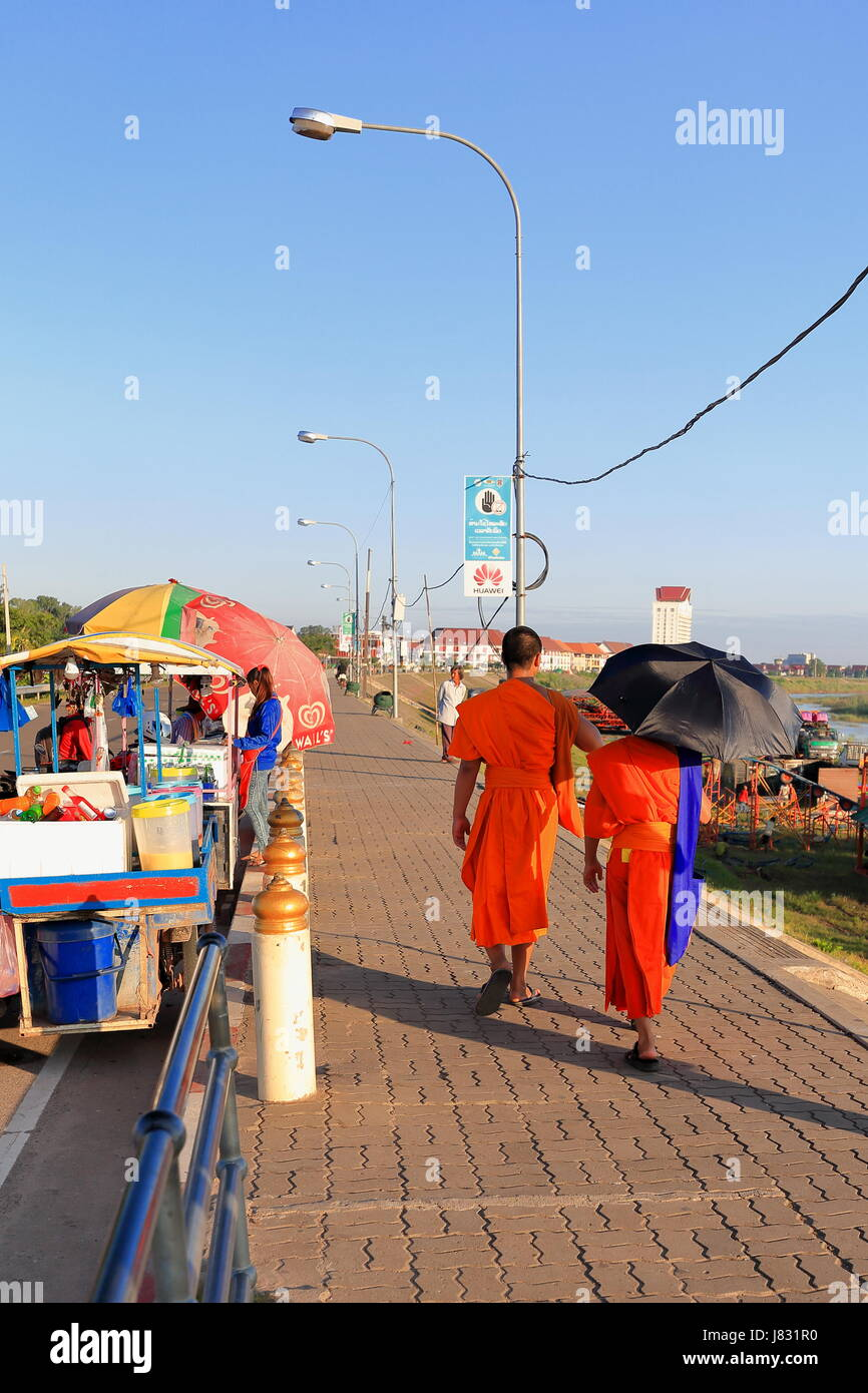 Vientiane, Laos-October 13, 2015: Pair of saffron dressed Buddhist monks stroll along the Quai Fa Ngum bordering - Stock Image