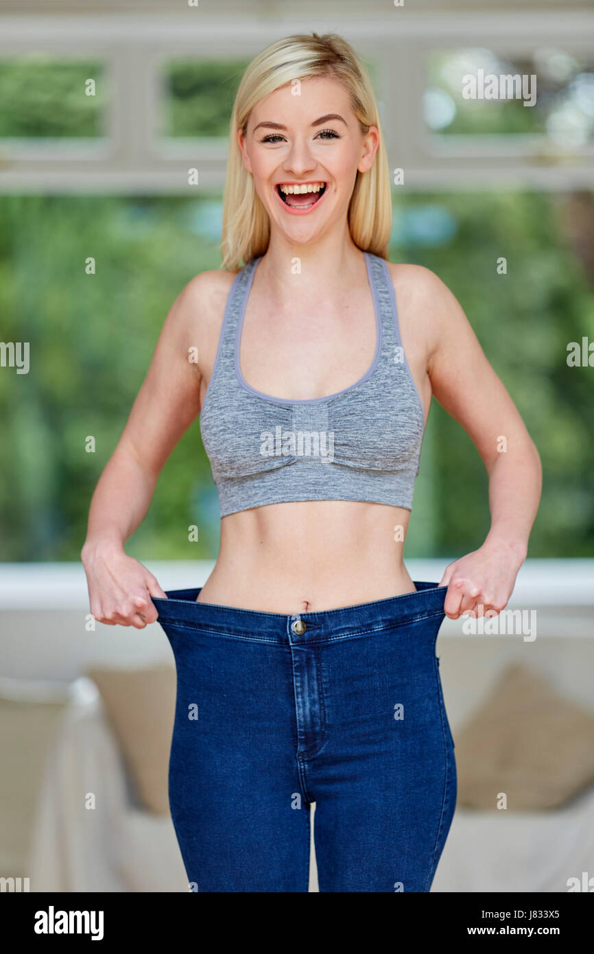 Girl wearing large jeans - weight loss - Stock Image