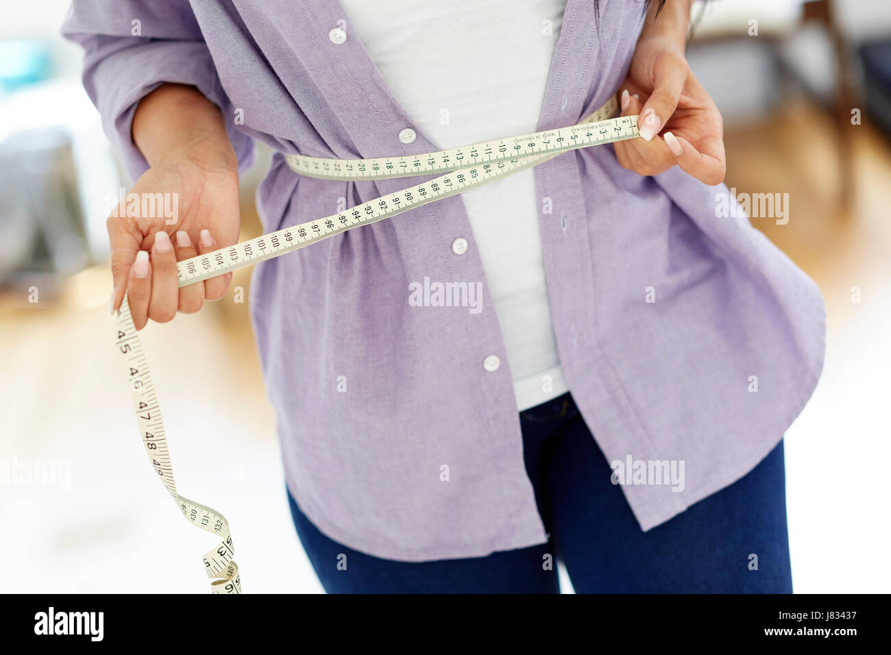Woman holding tape measure around her waist - Stock Image