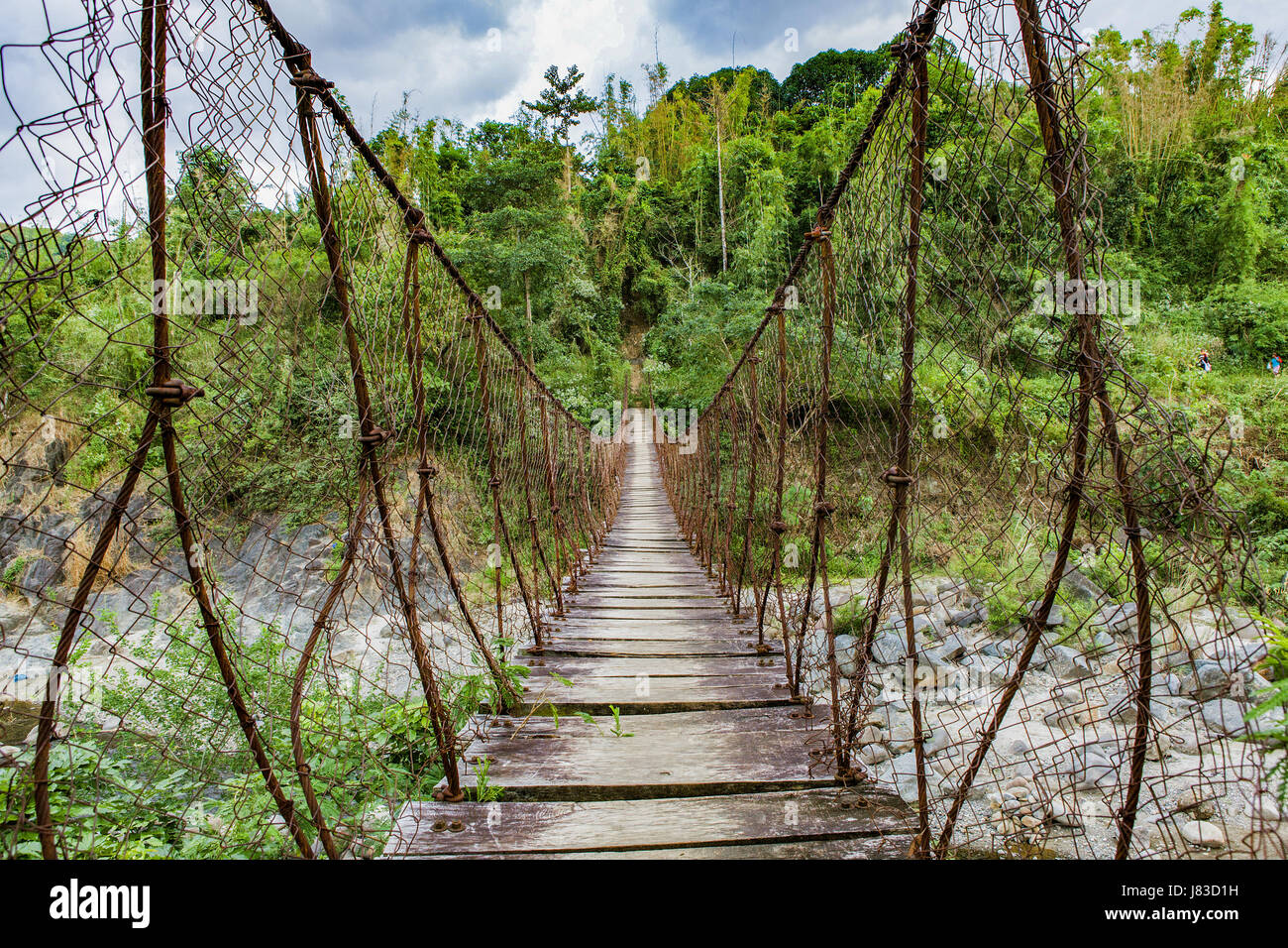 A suspension bridge made of cable, wire fencing and wood hangs over ...