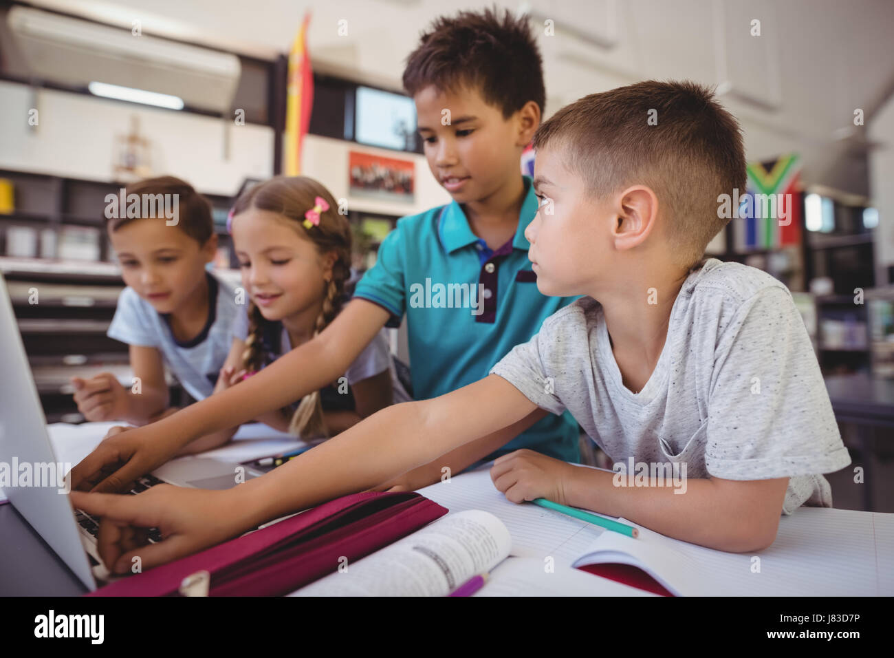 Attentive schoolkid using laptop in library at school - Stock Image