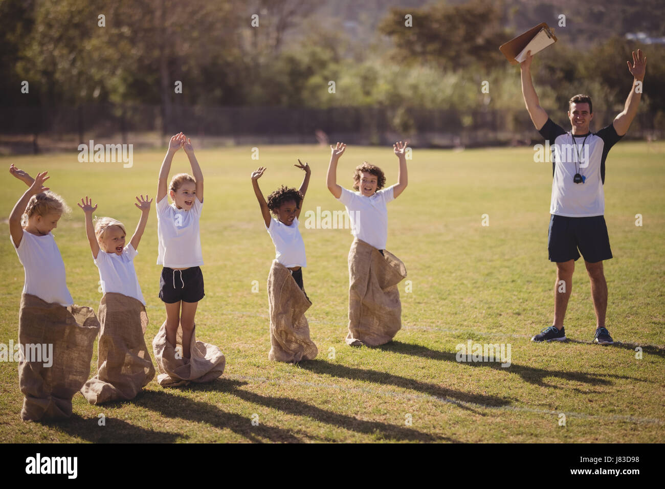 Coach and schoolgirls enjoying in park during sack race on a sunny day - Stock Image