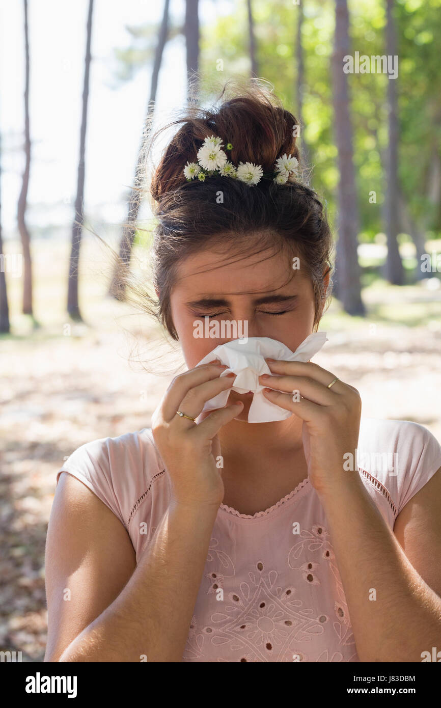 Woman suffering from cold and flu in the park - Stock Image
