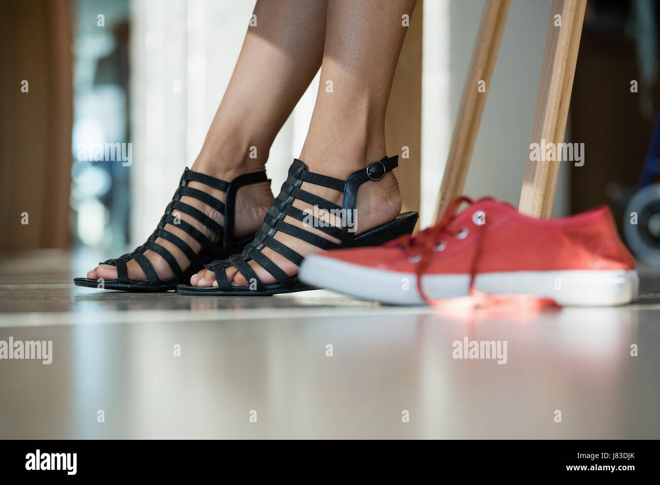 Low section of woman wearing black sandal in office - Stock Image