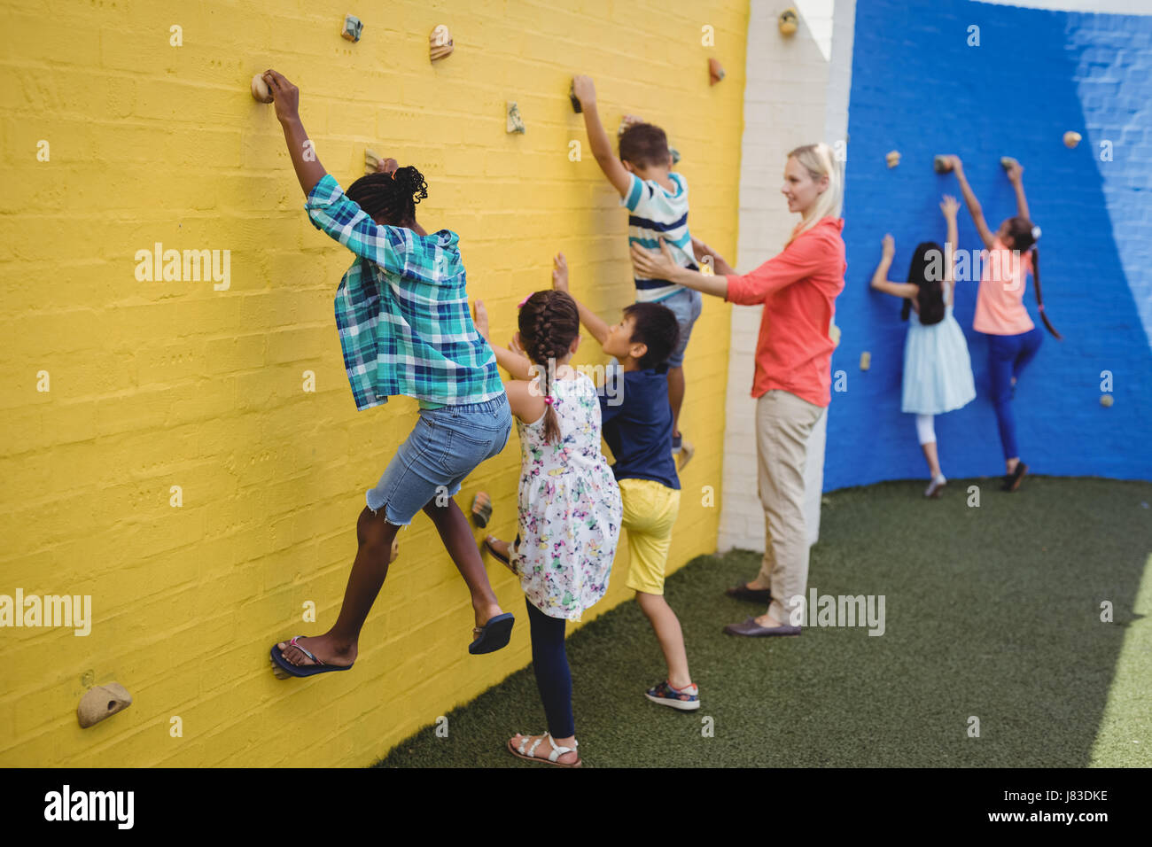 Trainer assisting kids in climbing wall in school - Stock Image