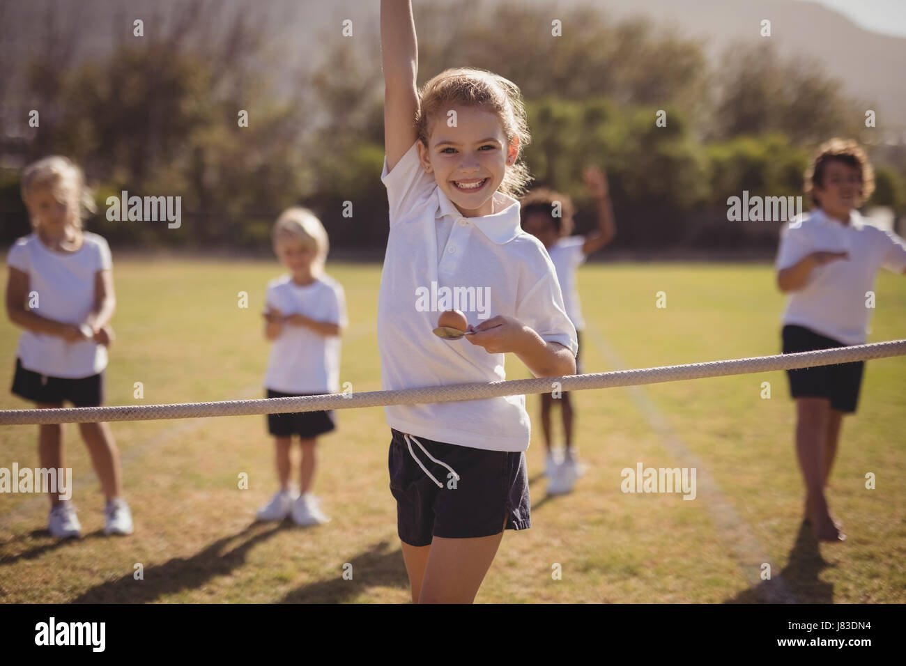 Portrait of happy schoolgirl wining egg and spoon race in park - Stock Image