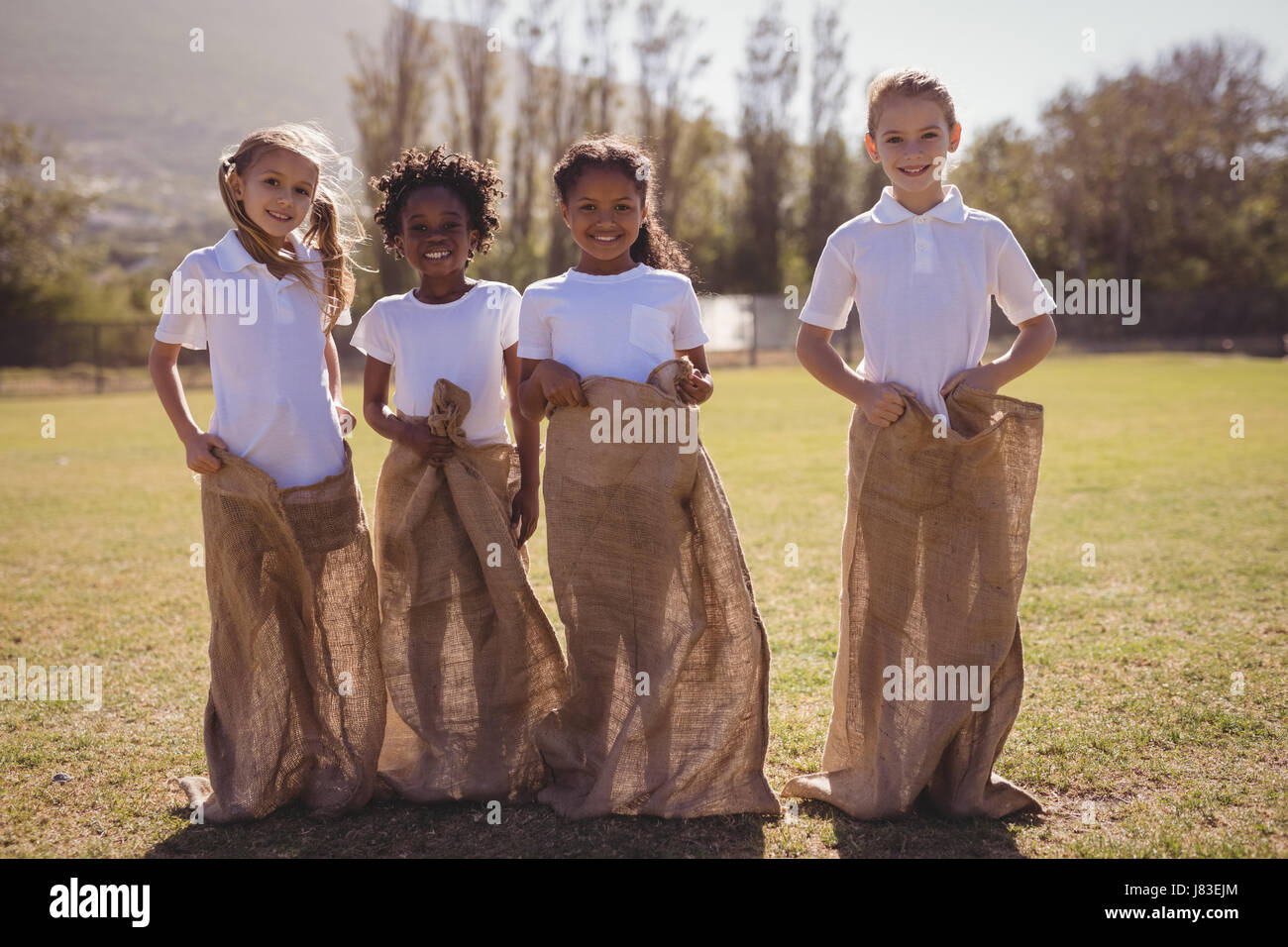 Portrait of happy schoolgirls standing in sack during race on a sunny day - Stock Image