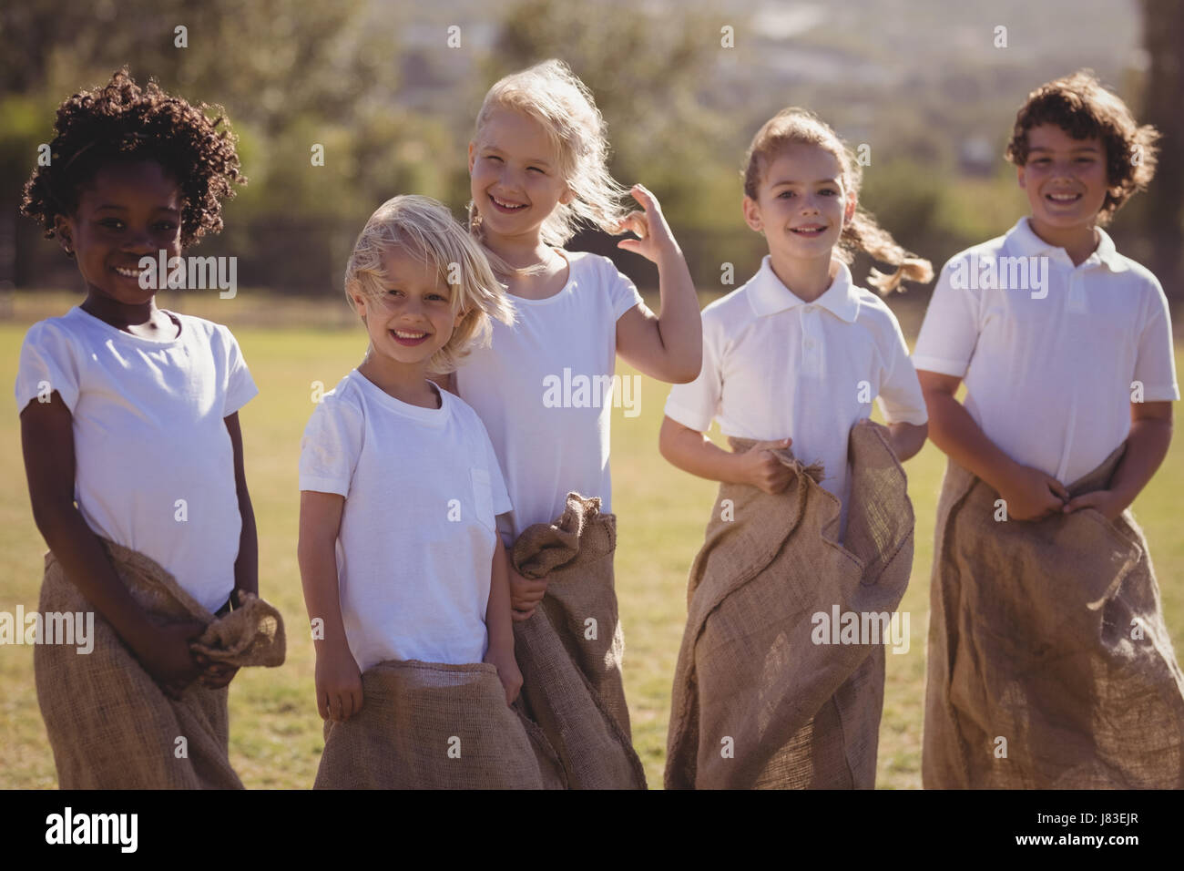 Happy schoolgirls having fun during sack race in park on a sunny day - Stock Image