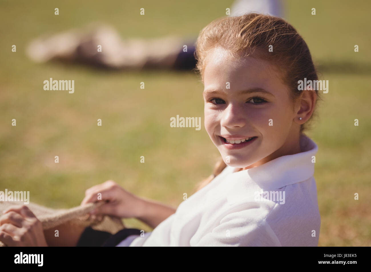 Portrait of happy schoolgirl preparing for sack race in park on a sunny day Stock Photo