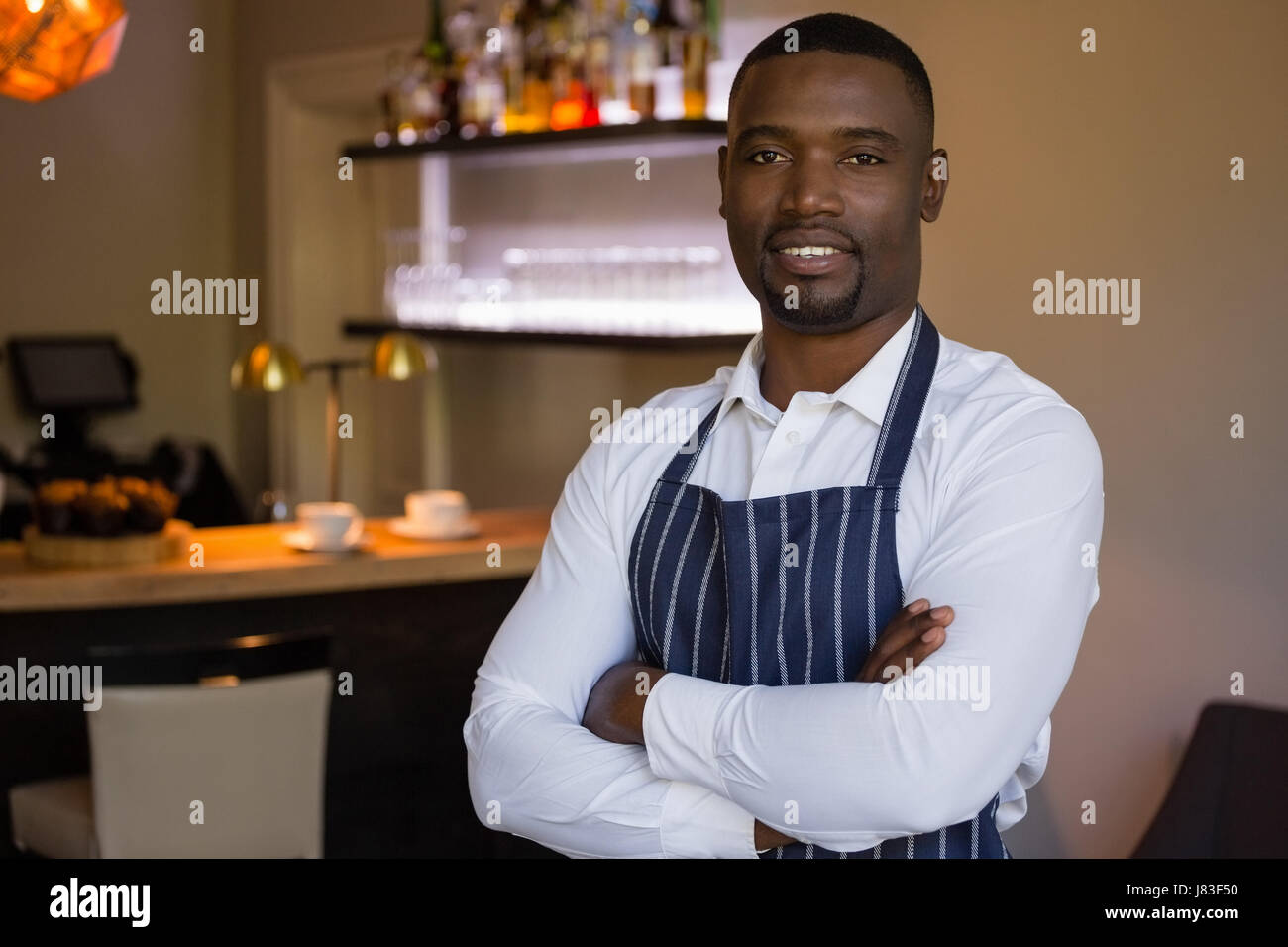 Portrait of confident waiter standing with arms crossed in restaurant - Stock Image