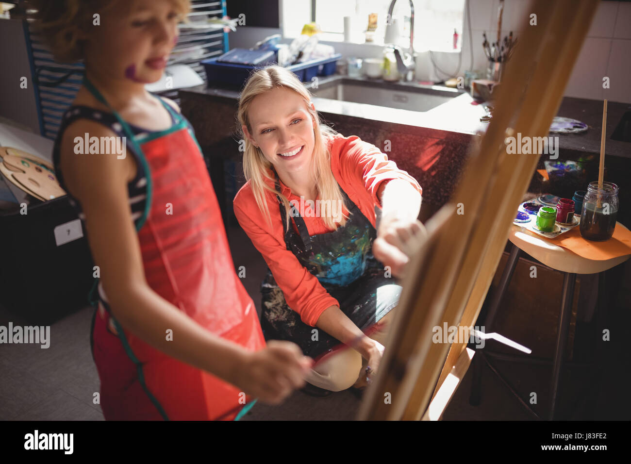 Teacher assisting girl in drawing class at school Stock Photo
